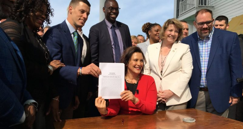 Michigan Gov. Gretchen Whitmer holds up a recently signed piece of no-fault insurance legislation