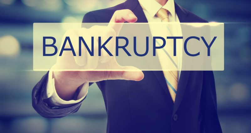 A man in a black suit holding up a rectangular sign that reads bankruptcy with one hand