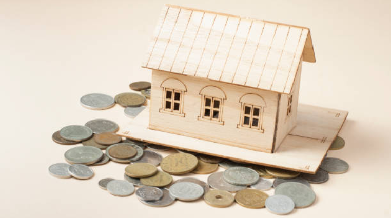 Coins scattered around a wooden model of a house.