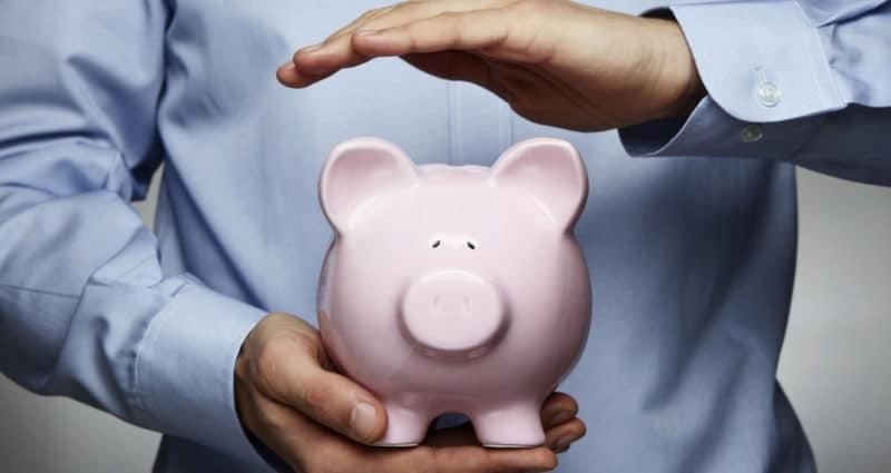 Man holding a pink porcelain piggy bank