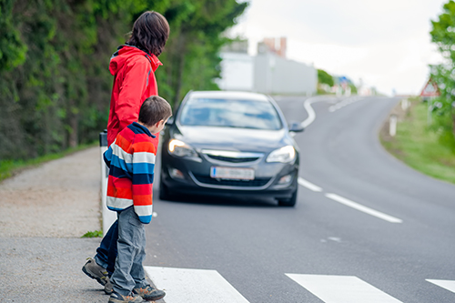 A parent and child cautiously walk toward a crosswalk as a grey sedan drives toward them.