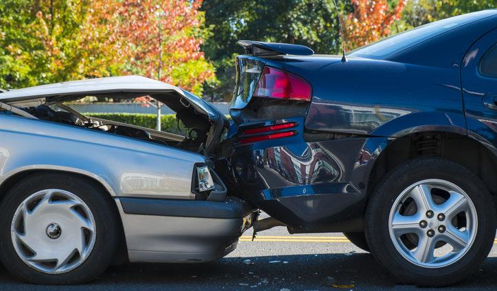 A grey sedan rear ends a black sports car in a crash causing significant damage.