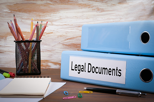 A binder of legal documents next to a container of pencils and a pad of paper.
