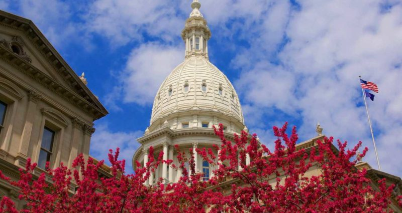 Red flowers frame the dome of the Michigan State Capitol Building