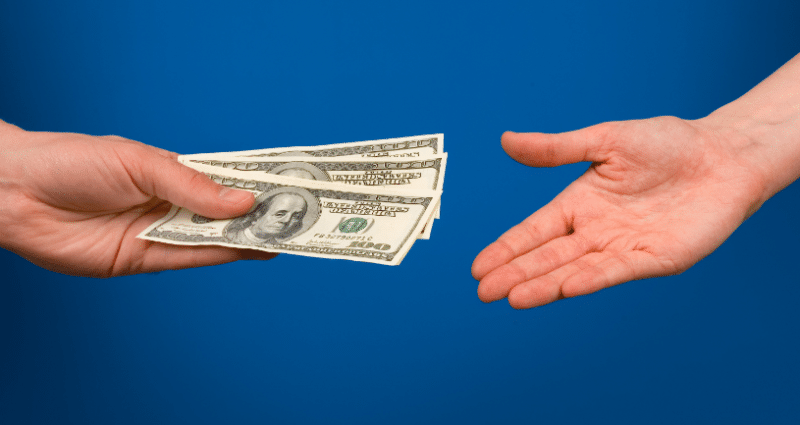 The hand on the left hands over three $100 bills to the hand on the right.