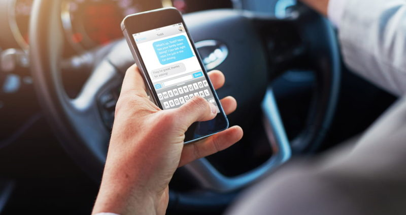 Closeup of a person texting on an iPhone while driving a vehicle