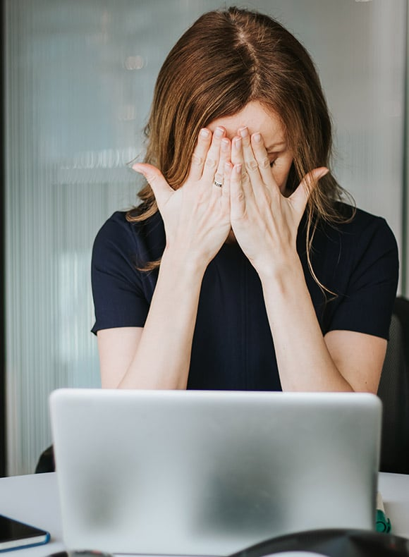 Distraught woman at a computer covering her face.